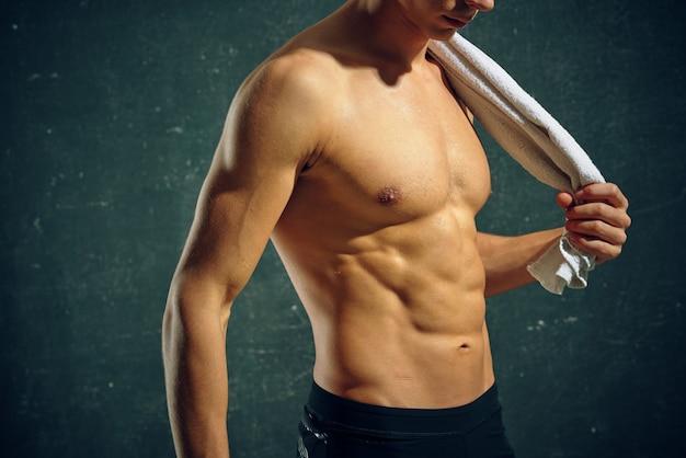 彼の手とトレーニング動機モデルでポンプアップされた胴体タオルを持つ男。高品質の写真