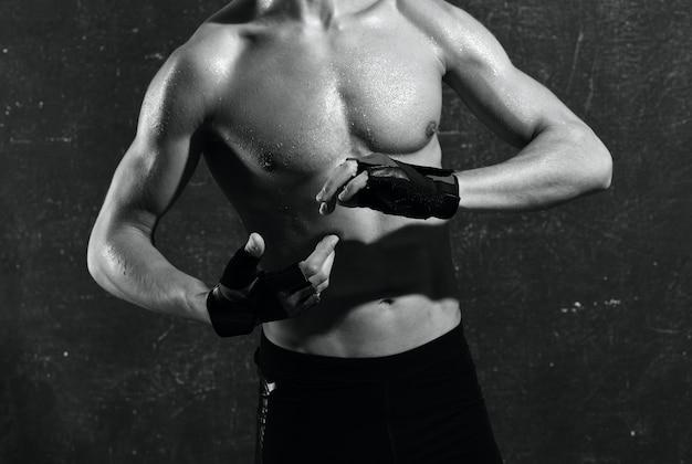 Человек с накачанным торсом в перчатках тренирует мышцы