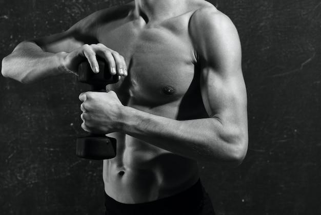 장갑 운동에 펌핑된 몸통을 가진 남자는 근육을 운동