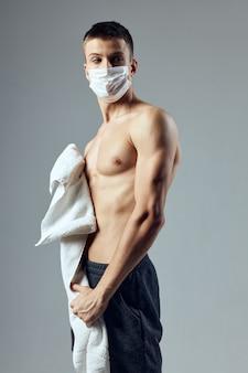 Человек с накачанным торсом, медицинская маска, защита от вирусов, тренажерный зал