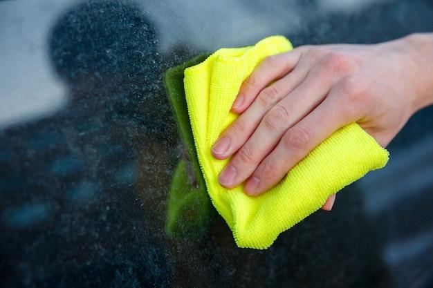 손에 헝겊을 든 남자가 자동차의 더러운 유리를 닦는다