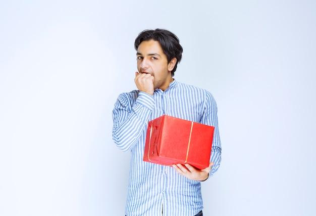 Мужчина с красной подарочной коробкой выглядит напуганным и напуганным. фото высокого качества