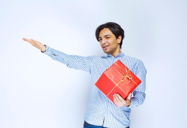 赤いギフトボックスを持った男性が、前の人に気づき、ギフトを贈るように呼びかけました。高品質の写真