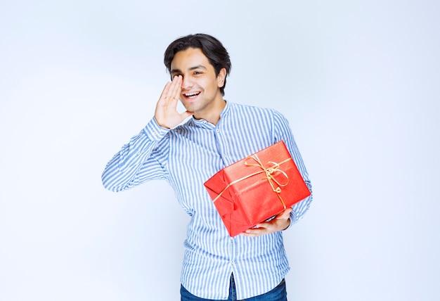 注意を叫ぶ赤いギフトボックスを持つ男。高品質の写真