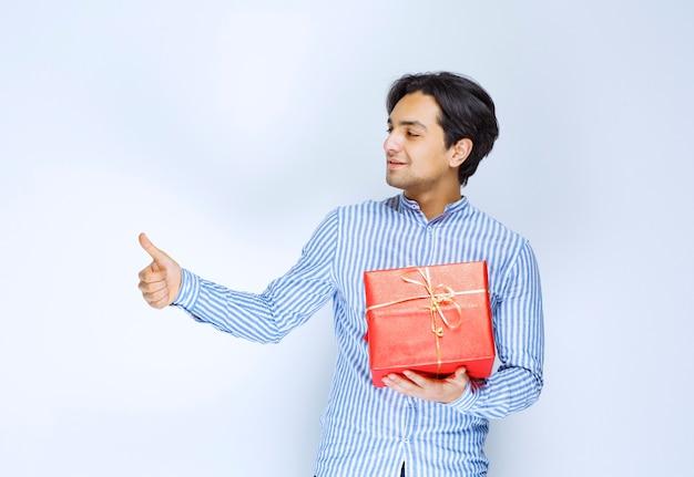 Человек с красной подарочной коробкой показывает палец вверх. фото высокого качества