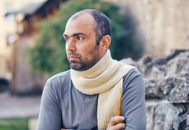 Мужчина с курительной трубкой. бородатый красивый молодой человек, держащий курительную трубку