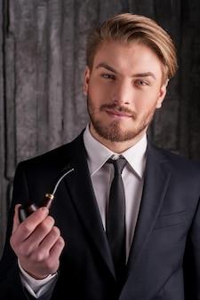 喫煙パイプを持つ男。喫煙パイプを保持し、カメラに笑みを浮かべて正装でハンサムな若い男の肖像画