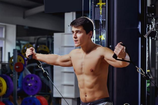 체육관에서 시뮬레이터에서 운동을 하 고 스포츠 그림을 가진 남자.