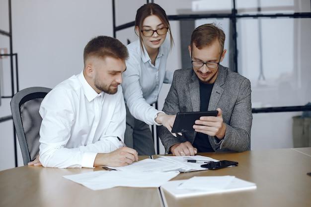 タブレットを持つ男。ビジネス会議でのビジネスパートナー。テーブルに座っている人