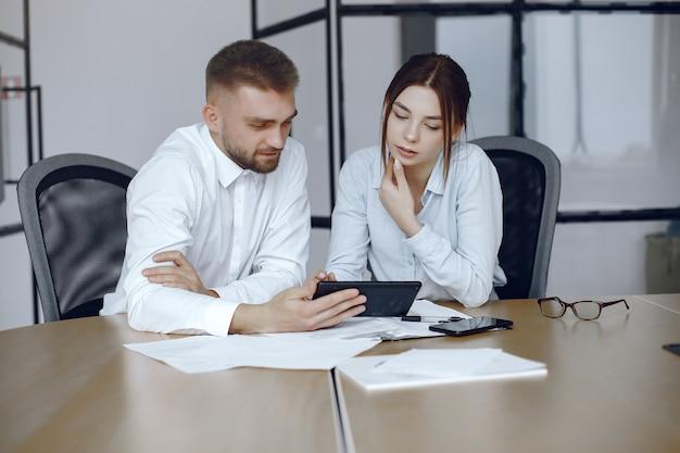 태블릿을 가진 남자입니다. 비즈니스 회의에서 비즈니스 파트너 테이블에 앉아 사람들