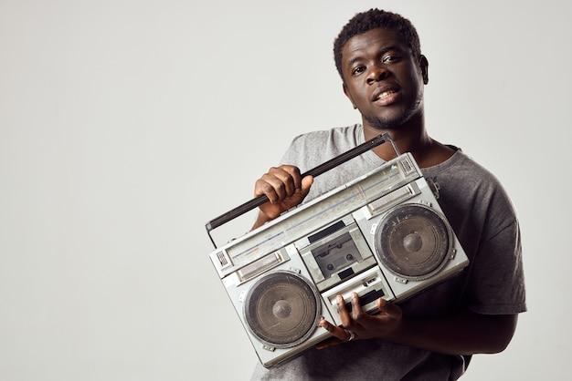 Человек с магнитофоном в руках слушает музыку африканского образа жизни
