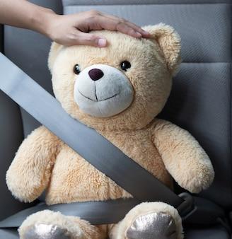 Человек с плюшевым мишкой, пристегнутый ремнем безопасности в машине