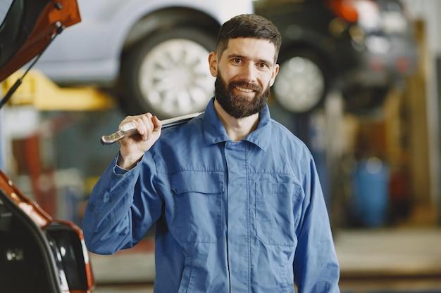 オーバーオールの車の近くのガレージでツールを持つ男