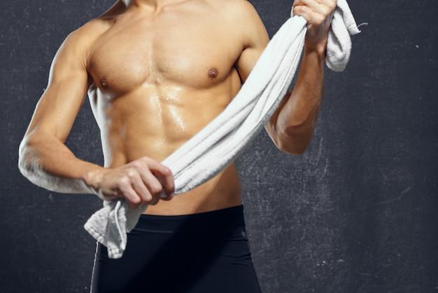 手にタオルを持った男が体を動かし、フィットネスポーズをとる。高品質の写真