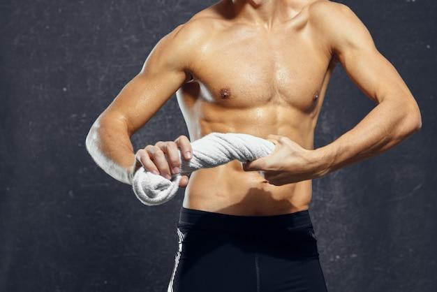 手にタオルを持った男が体を動かし、フィットネスポーズをとる