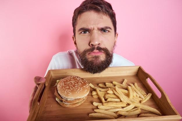 手に食べ物のトレイを持った男ハンバーガーフライとファーストフードのカロリーピンクの壁の肖像画のクローズアップ。