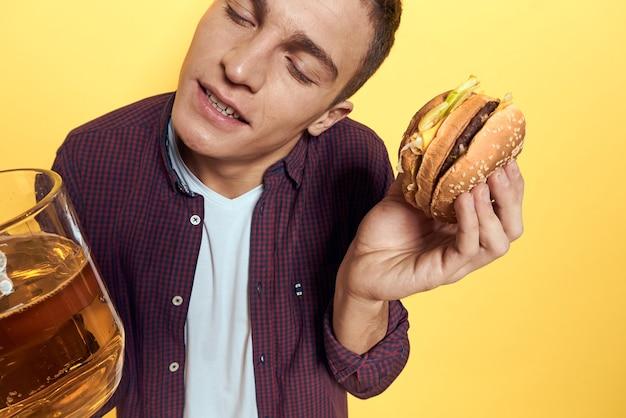 Человек с подносом нездоровой пищи: гамбургер и картофель, пиво