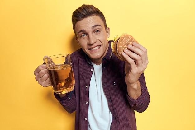 Человек с подносом гамбургера нездоровой пищи и картофеля фри, пива