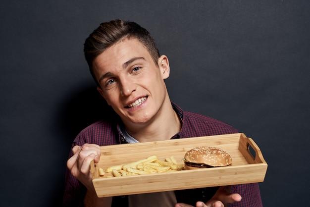 Человек с подносом нездоровой пищи, гамбургера и картофеля фри