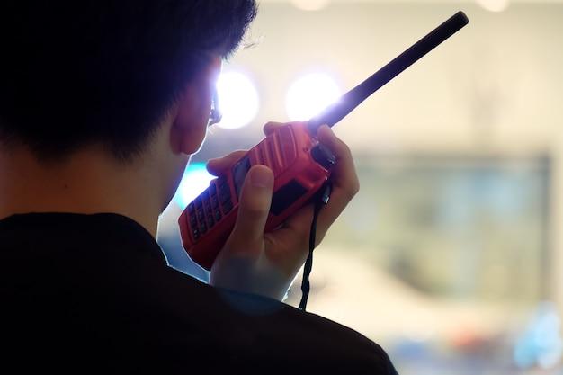 Человек с walkie talkie или портативный радиоприемопередатчик для связи