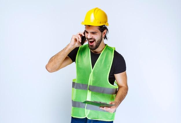 黄色いヘルメットとフォルダーを持った男が電話に向かって叫んでいます。