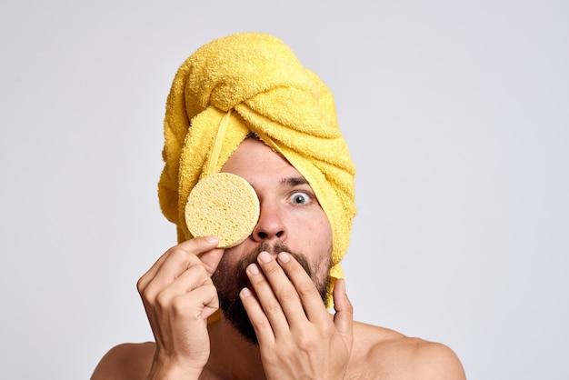 Мужчина с желтым полотенцем на голове, голые плечи, губка для чистой кожи, уход за лицом, свет