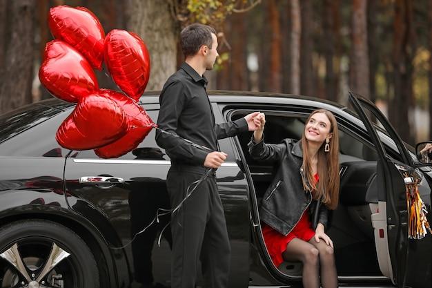 彼のガールフレンドが車から降りるのを手伝っている気球を持つ男。バレンタインデーのお祝い