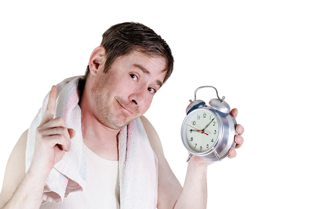 The man with the alarm clock slept in the morning. towel over the shoulders. funny facial expression. the index finger raised to the top. isolated white background.