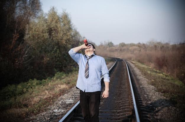 屋外の線路にアルコールを持つ男。旅行のコンセプト。孤独な人。自殺の概念。うつ病。