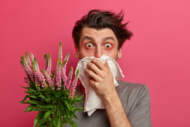 Man with allergy sneezes and covers nose with napkin, listens advice from allergist how to cure hay fever, has red watery eyes, needs to treat allergic rhinitis, isolated on pink wall.
