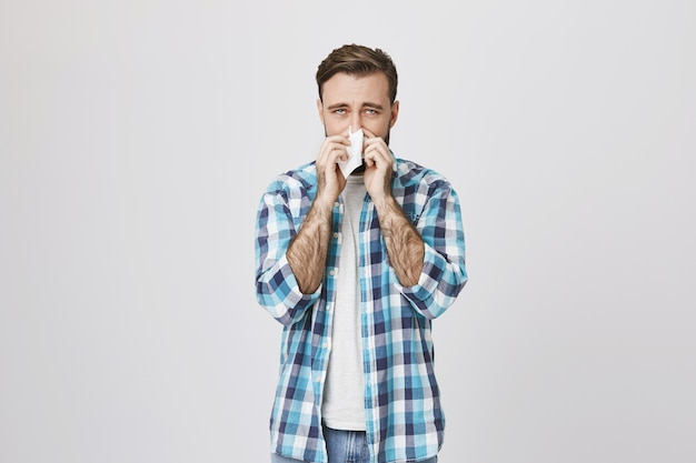 Man with allergy sneezing in tissue
