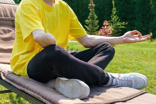 Человек с ампутированной рукой тренируется с резинкой на открытом воздухе