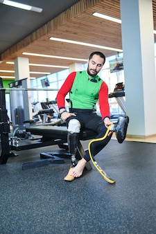 Человек с ампутированной ногой меняет протез