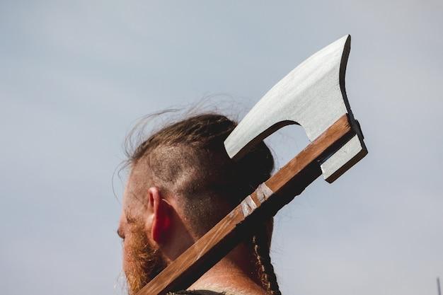 Человек с топором за плечом крупным планом в солнечную погоду