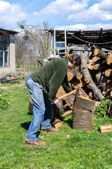 Мужчина топором рубит бревно на заднем дворе, дрова на зиму