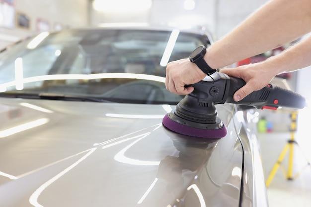 販売コンセプトのために車を準備する車のワークショップ研磨車で軌道研磨機を持つ男
