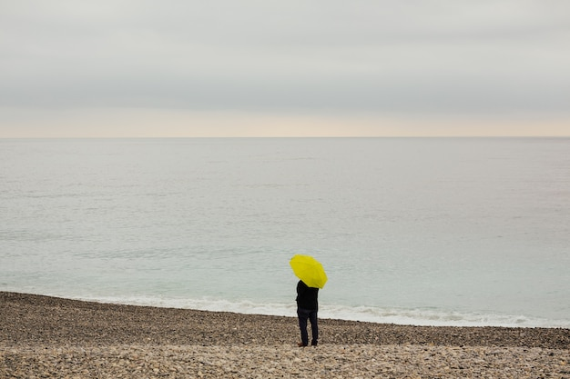 Человек с желтым зонтом на берегу средиземного моря
