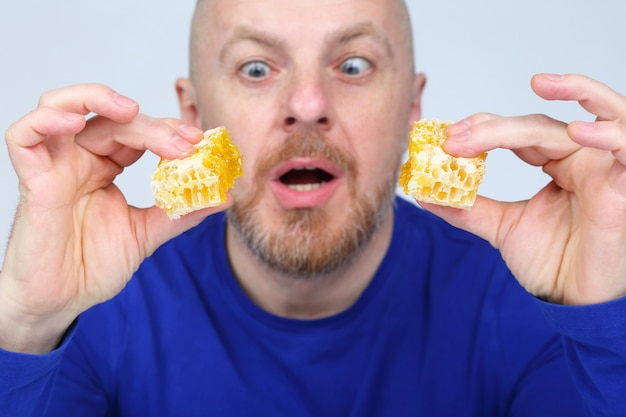 Man with an appetite looks at two pieces of honeycomb honey in his hands