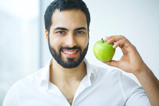 アップルを持つ男。白い笑顔、健康な歯を持つ美しい男性。高解像度画像。