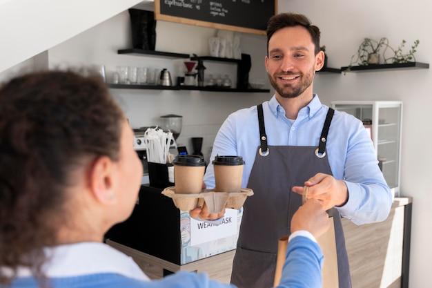 Uomo con grembiule che offre cibo da asporto confezionato a una cliente femminile
