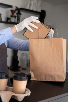 持ち帰り用の食品を準備するエプロンを持つ男