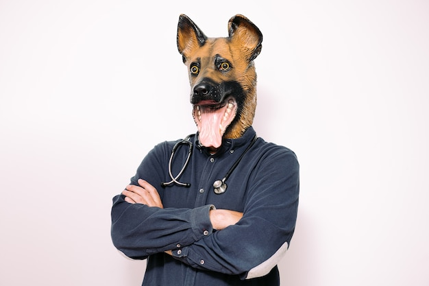 Man with arms crossed and dog mask and stethoscope