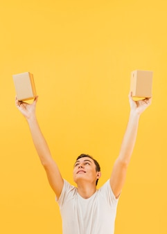 Man with arms raised holding small packages