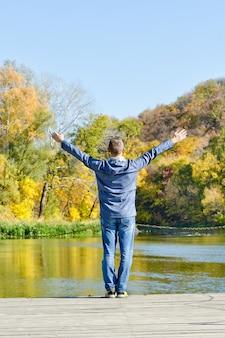 ドックに立って腕を上げた男。秋、晴れ。背面図