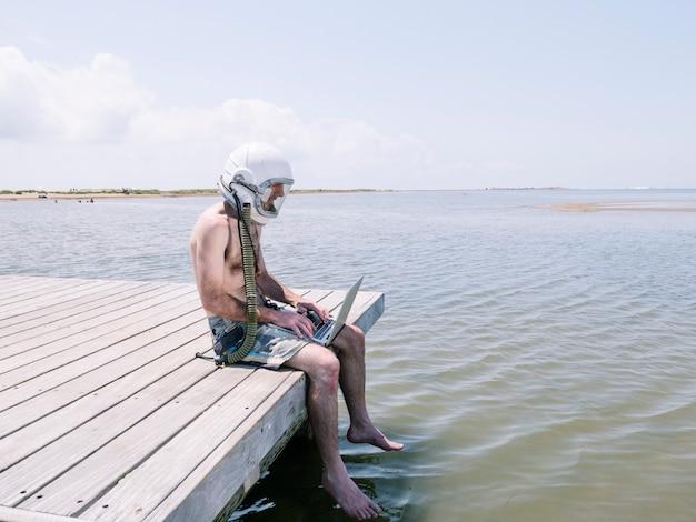 Человек с шлемом космонавта и ноутбуком на пляже