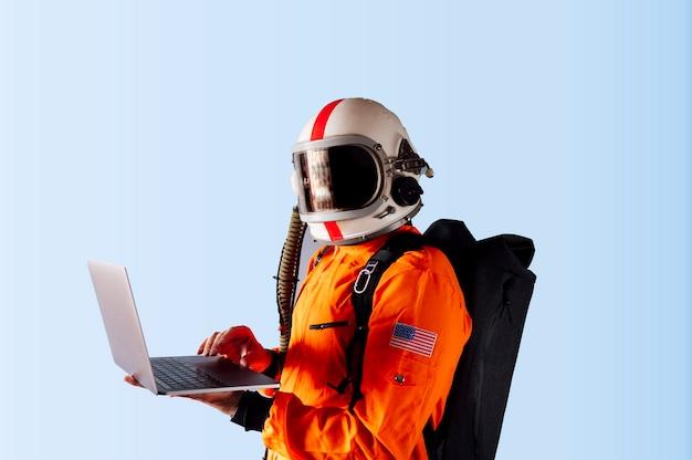 Человек с шлемом космонавта и ноутбуком