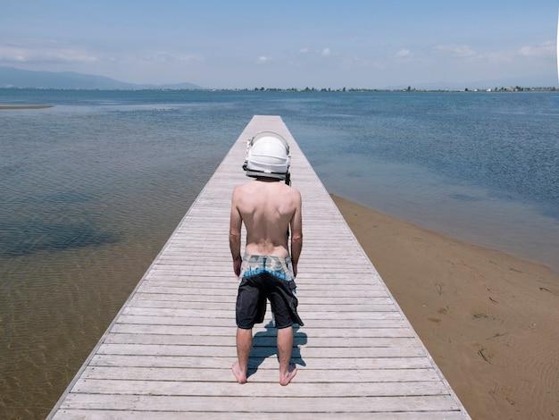 Человек в шлеме космонавта на пляже