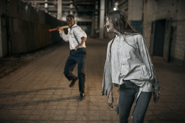 Man with axe attacked female zombie in abandoned factory, scary place. horror in city, creepy crawlies, doomsday apocalypse, bloody evil monsters