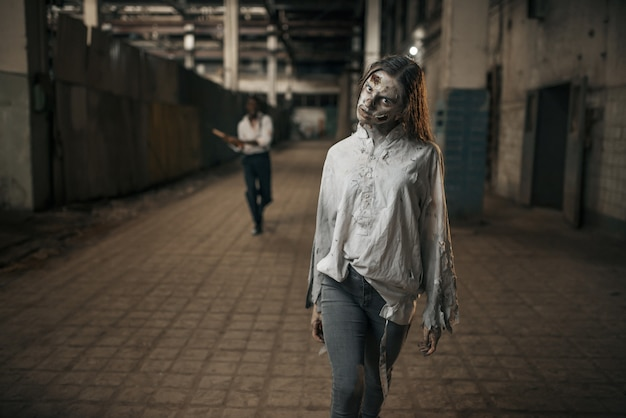 廃工場、怖い場所で女性ゾンビに追いつく斧を持つ男。都市の恐怖、不気味な這いつくばり、終末の黙示録、血まみれの邪悪なモンスター
