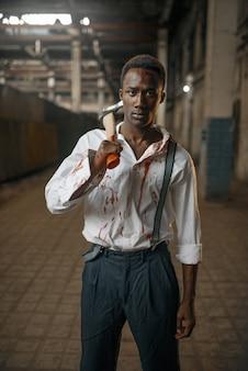 廃工場、ゾンビの土地で斧を持つ男。都市の恐怖、不気味な這いつくばり、終末の黙示録、血まみれの邪悪なモンスター